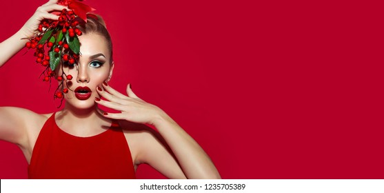 Beautiful young girl with red lipstick on a red background holding a branch with red berries. Christmas.fashion, beauty, makeup, cosmetics, beauty salon, style, personal care, posture, hair.
