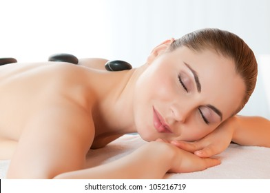 Beautiful young girl relaxing with hot stones on back for a therapy at spa