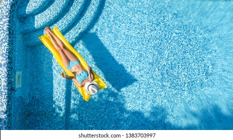 Beautiful young girl relaxing in swimming pool, swims on inflatable mattress and has fun in water on family vacation, tropical holiday resort, aerial drone view from above
