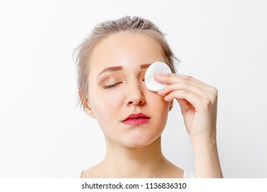 Beautiful young girl removes make-up with cotton pad in studio, close up portrait