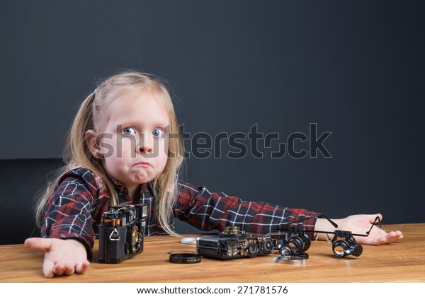 Beautiful young girl repairing a broken vintage film camera