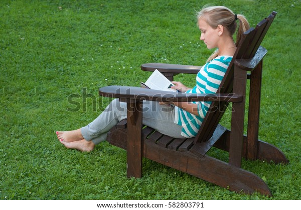 beautiful young girl is resting in a chair with a magazine on a green lawn