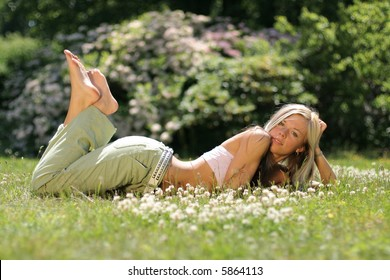 Beautiful young girl rests in the grass