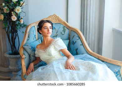 beautiful young girl in rich dress lying on sofa, relax concept