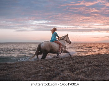 beautiful young girl riding a horse walking along the sandy beach at sunset time
