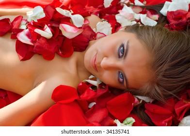 Beautiful young girl in rose petal. Spa resort