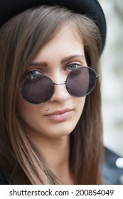 Beautiful young girl with round sunglasses and black hat