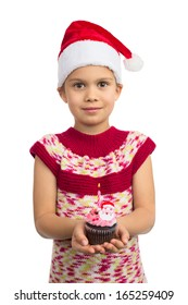 Beautiful young girl in Santa hat holds colorful cupcake with toy Santa on top of it, isolated