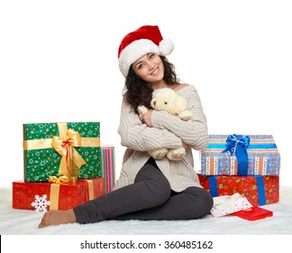 beautiful young girl in santa hat with teddy bear toy and gift boxes, white background
