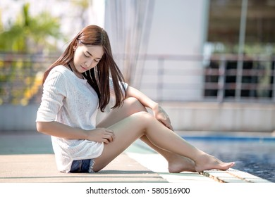 Beautiful young girl seats at the swimming pool in the summer.