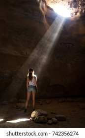 Beautiful young girl seeing the light, having spiritual experience in sunbeam while alone in a cave