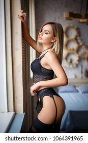 Beautiful young girl in a sexy black lingerie and stockings