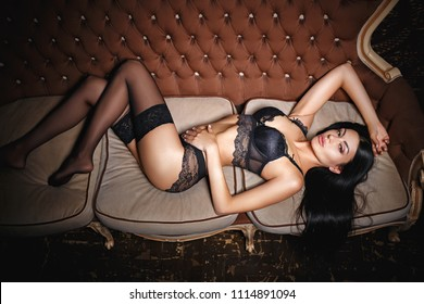 Beautiful young girl in a sexy black lingerie on sofa