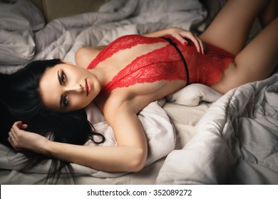 Beautiful young girl in  sexy red lingerie on a bed
