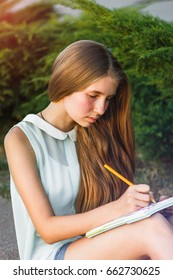 Beautiful young girl in shorts sitting in the park and writing with a pencil in a notebook, the bright sun shines