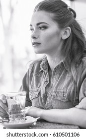 Beautiful young girl sits in a cafe, looks out the window and drinks tea. Photo with granularity