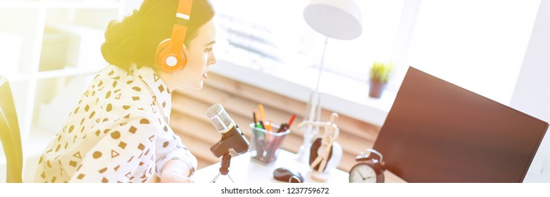 Beautiful young girl sits in headphones and with a notepad at the table in the office and speaks into the microphone.