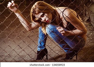 Beautiful young girl sitting behind the metallic lattice