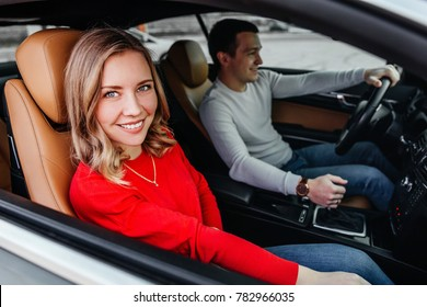 Beautiful young girl sitting in the car next to her boyfriend
