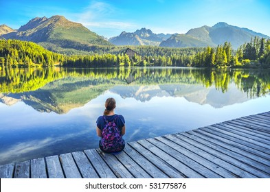 Beautiful young girl sitting near by clear lake under wonderful mountains in High Tatras - Slovakia. Morning light on Strbske pleso lake. Photo before touristic trip. Freedom concept
