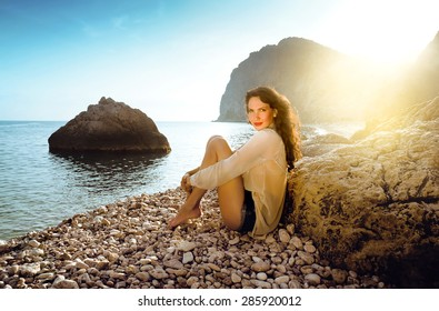 beautiful young girl sitting on the beach alone