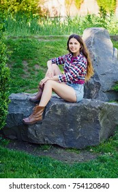 beautiful young girl sitting on a large stone in a park dressed in shorts and a shirt in a crate