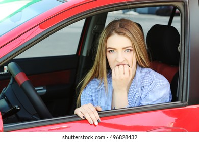 Beautiful young girl sitting in red car