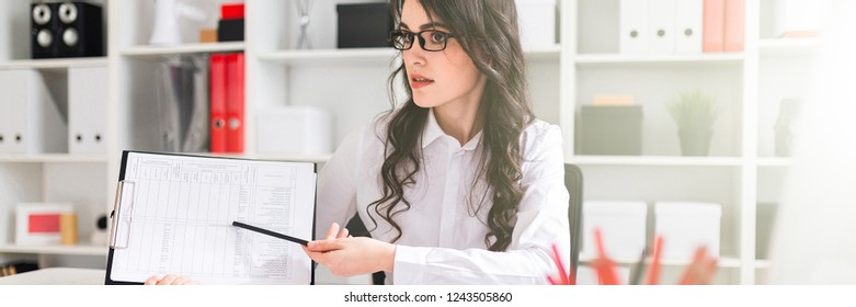 A beautiful young girl is sitting at a table in the office and pointing a pencil at the information in the document.