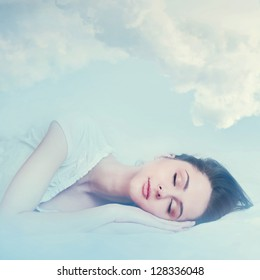 beautiful young girl sleeping and dreaming in the clouds