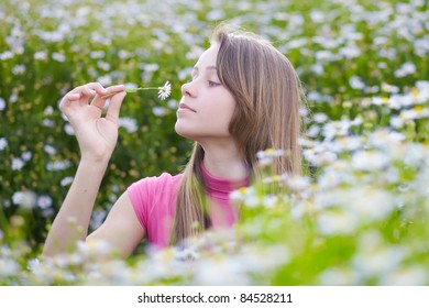 beautiful young girl smelling camomiles