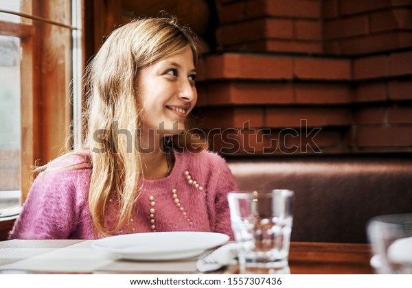beautiful young girl smiles in a cafe. on the table is a dish