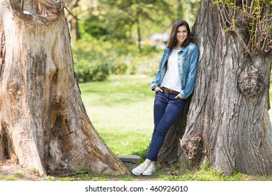 Beautiful young girl smiling and leaning on a tree