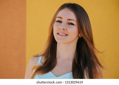 Beautiful young girl smiling portrait, simple look with yellow background