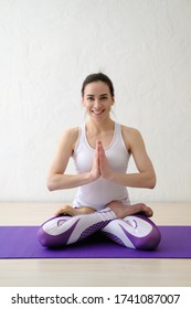 Beautiful young girl smiling and sitting in lotus position. Fitness, yoga instructor. Beautiful smiling confident young woman pretty face looking at camera posing alone at home in office