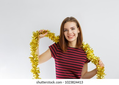 beautiful young girl smiling standing on white background and with tinsel of gold color on neck