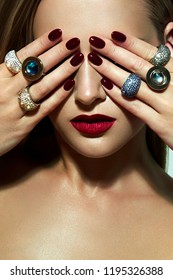 A beautiful young girl with smooth skin and an elegant hairstyle closes her eyes with her hands. Beautiful expensive rings on the fingers.