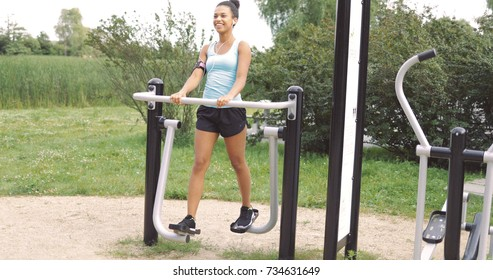 Beautiful young girl in sportswear using smartphone listening to music while working out on exerciser on background of summer park.