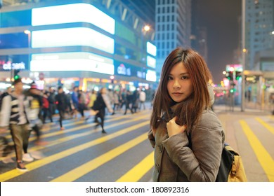 Beautiful young girl stand out and watching at night in hong kong, lost in city , busy crowd and yellow zebra crossing blurred background