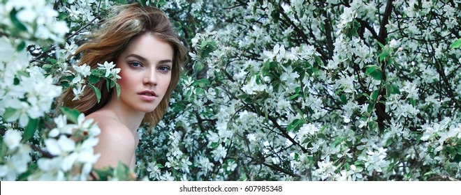 A beautiful young girl stands among the flowering trees. White flowers. Spring. A girl with her hair in a white dress. Portrait. Romance.