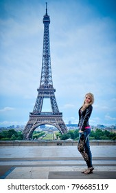 Beautiful Young Girl stands happy on the Background of the Eiffel Tower in Paris, vacation fun fun Travel, trip to Europe France Chic Luxury tour, holiday abroad study tourist excursion guide