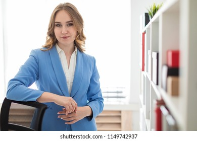 A beautiful young girl stands near a rack in the office, putting an elbow in the back of a chair.