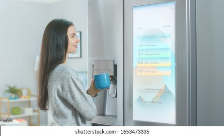 Beautiful Young Girl Stands Next to a Refrigerator While Drinking Her Morning Coffee. She is Checking the Weather Forecast and a To Do List on a Smart Fridge at Home. Kitchen is Bright and Cozy.