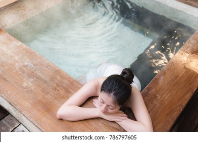 beautiful young girl stay on wooden poolside while steam water on the background