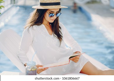 A beautiful young girl in a straw hat sitting on a summer terrace by the pool with book and cocktail