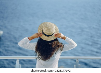 A beautiful young girl in a straw hat standing on a summer terrace and looking at the ocean
