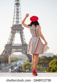A beautiful young girl in a striped multi-colored dress and a red beret is dancing against the backdrop of the Eiffel Tower in Paris.