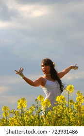 A beautiful young girl strolls through a rape seed field on a summer evening. Feeling carefree and serene she admires the colorful yellow flowers as the sun passes through them.