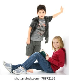 Beautiful young girl student with book sitting against the wall.  Boy standing behind her.