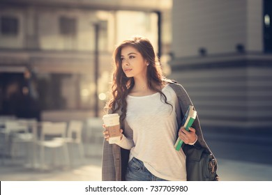 Beautiful young girl student drinking caffee on the way to college or university. Fashion dressed for school carrying her books and notebook wearing sunglasses. Lifestyle in the city back to school