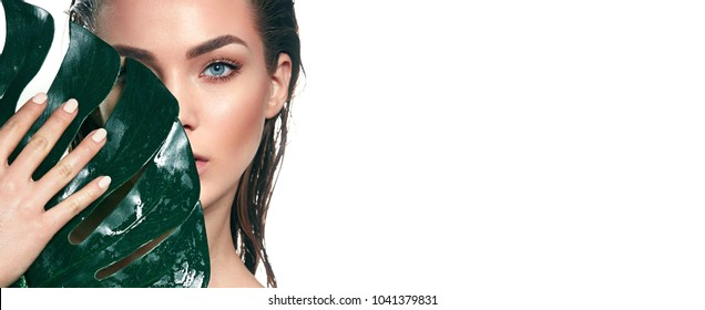 A beautiful young girl in the studio on a white background with wet skin and wet hair holds a large green tropical leaf in hands and covers a part of her face.Fashion, beauty, make-up, cosmetics.